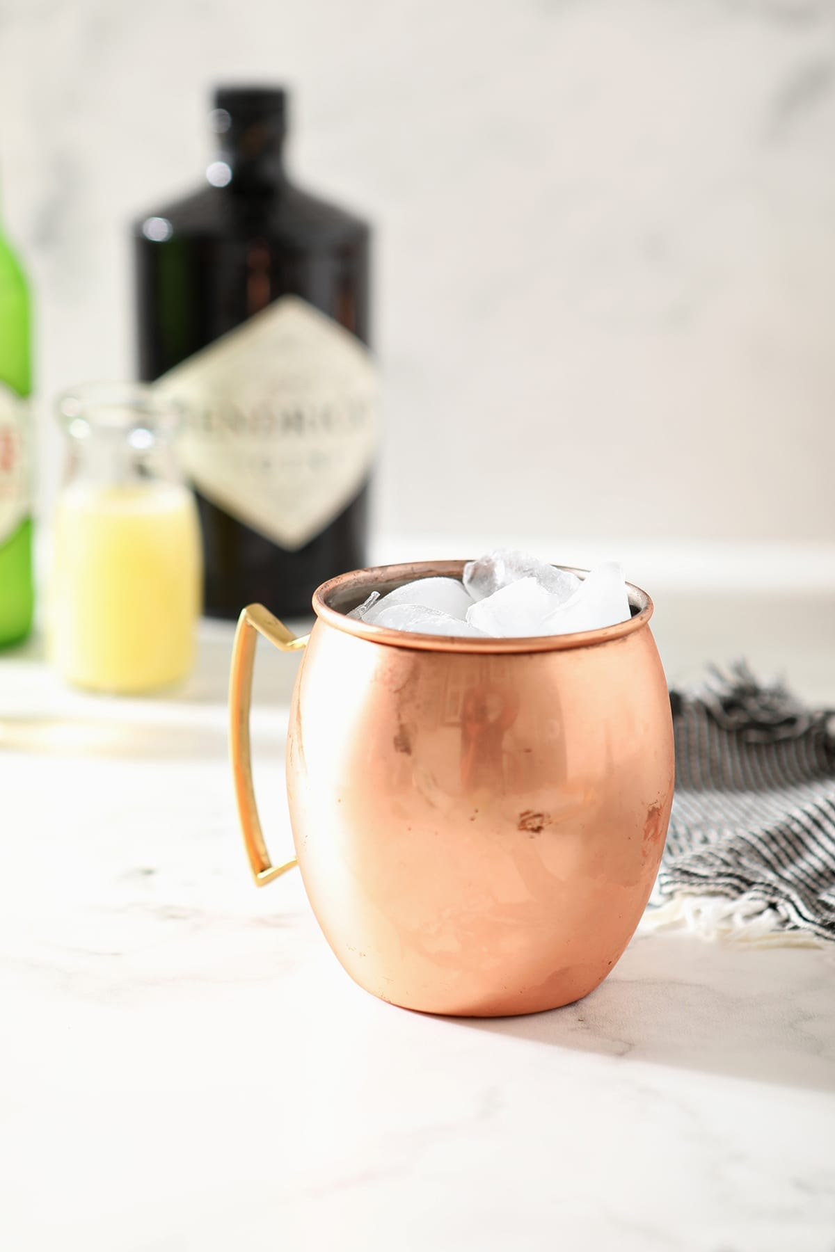 A copper mug full of ice sits on a marble surface in front of a bottle of gin, ginger beer and lime juice