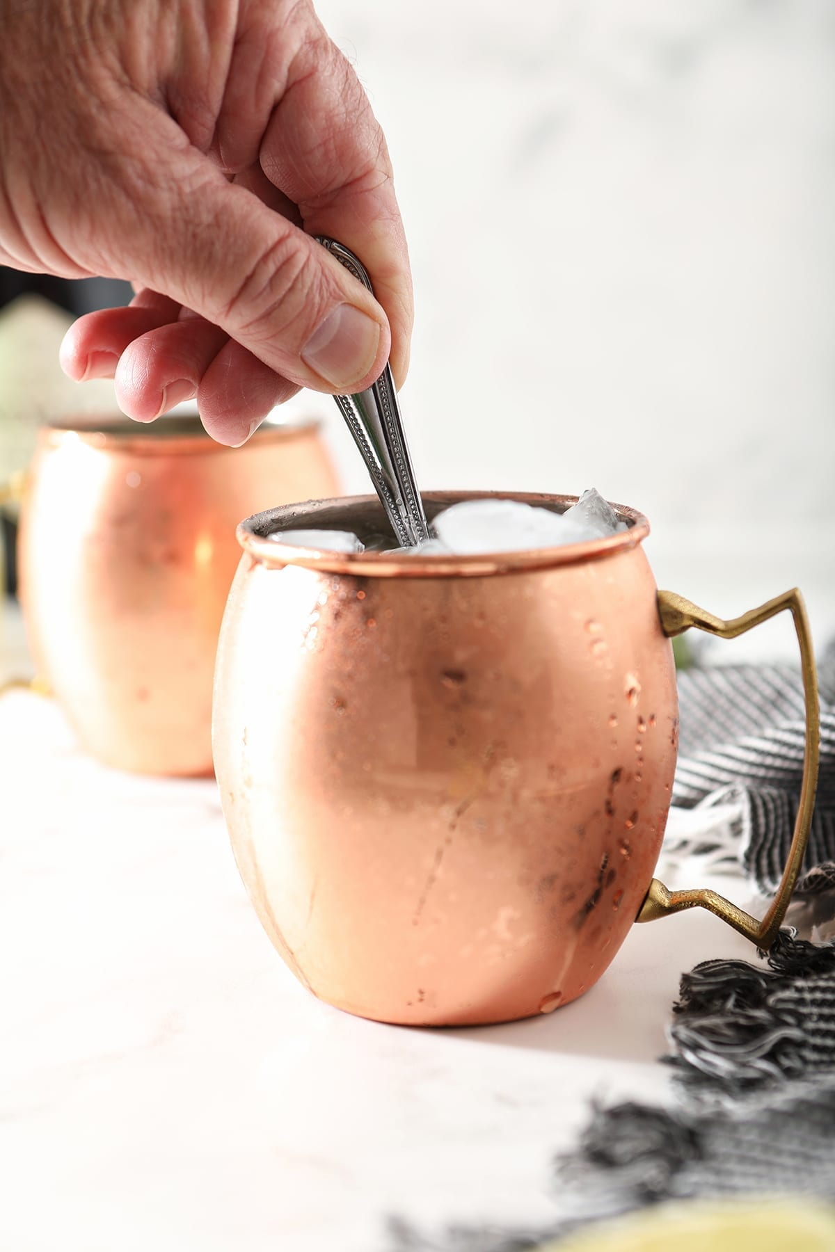 A person uses a silver spoon to stir ingredients inside a copper mug