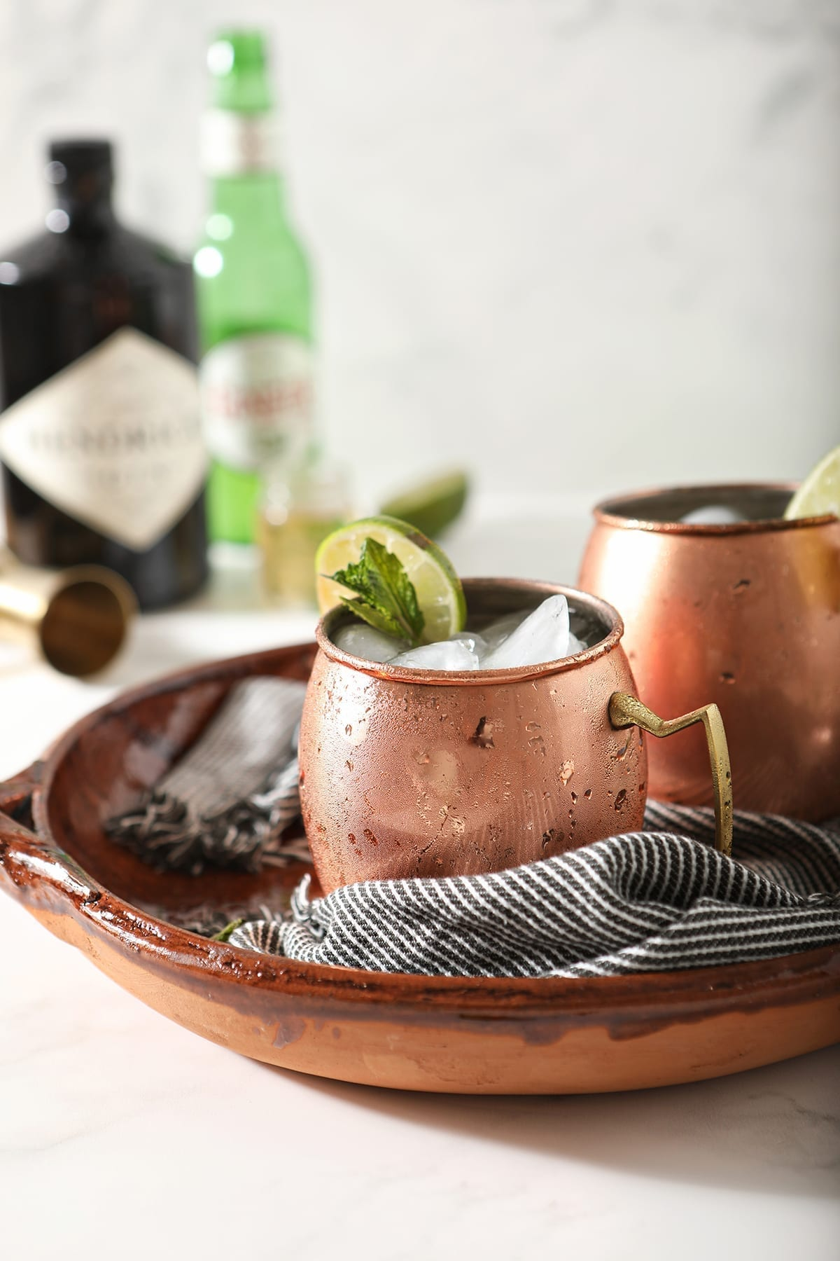 Two copper mugs garnished with lime rounds and mint are shown in a brown serving tray holding Gin Gin Mules