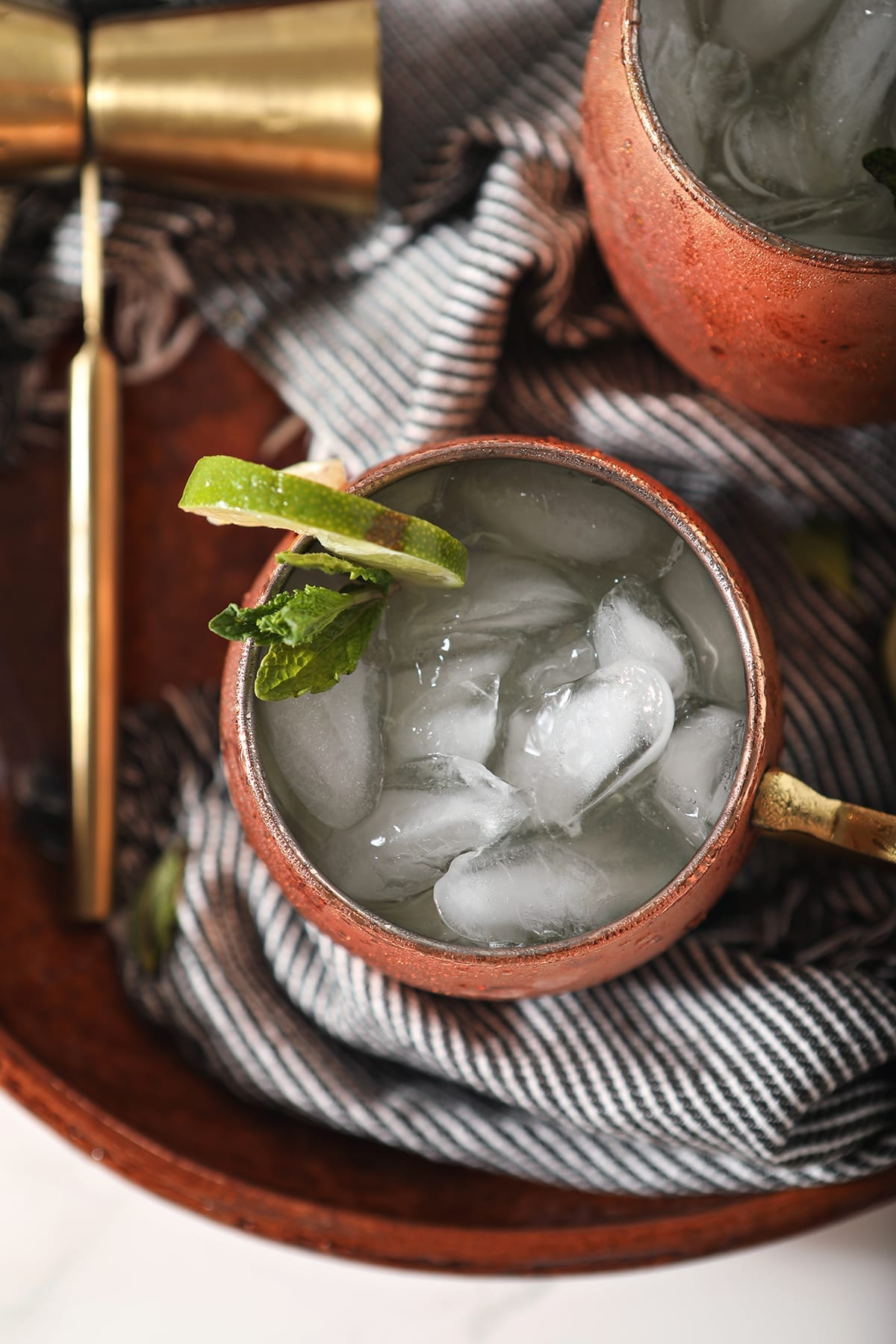 Overhead close up of a mule mug holding a Gin Gin Mule on top of a blue striped towel on a brown serving platter