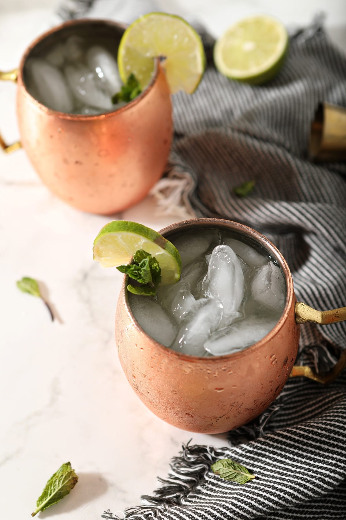 Two Gin Gin Mules in copper mugs on a marble surface sit next to a blue striped towel, lime rounds and mint leaves