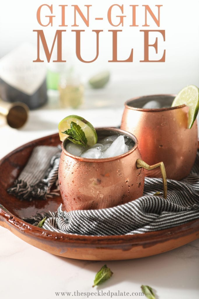 "Two copper mugs ga rnished with lime rounds and mint are shown in a brown serving tray holding Gin Gin Mules, with text stating ""Gin-Gin Mule"""