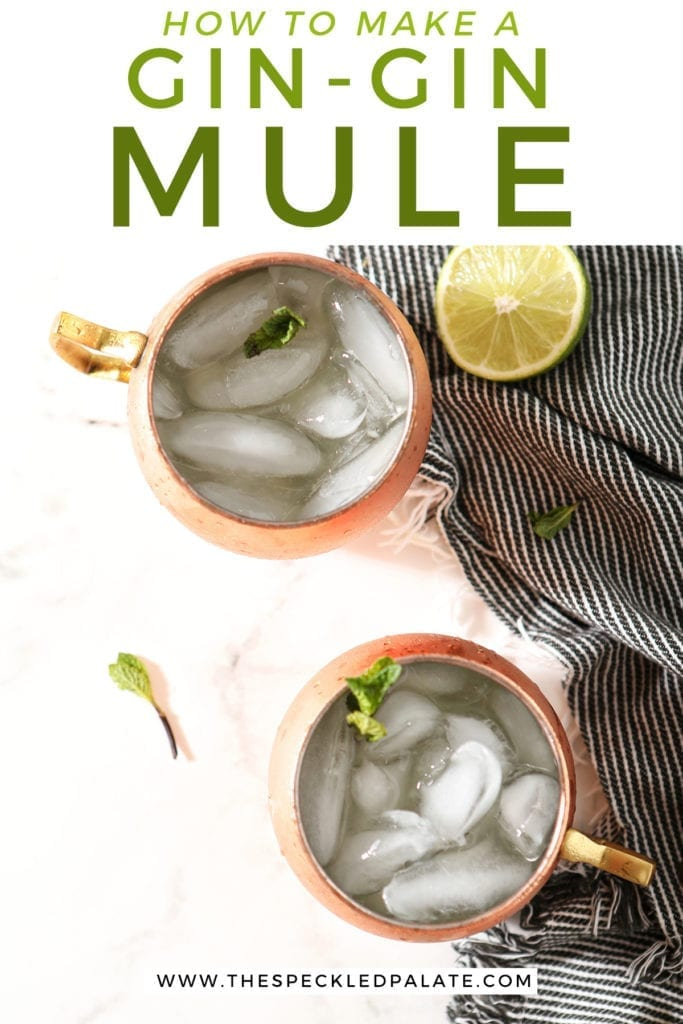 "Two Gin Gin Mules in copper mugs on a marble surface sit next to a blue striped towel, lime rounds and mint leaves, with text stating ""How to Make a Gin-Gin Mule"""