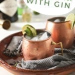 "Two copper mugs garnished with lime rounds and mint are shown in a brown serving tray holding Gin Gin Mules, with text stating ""How to Make a Moscow Mule with Gin"""