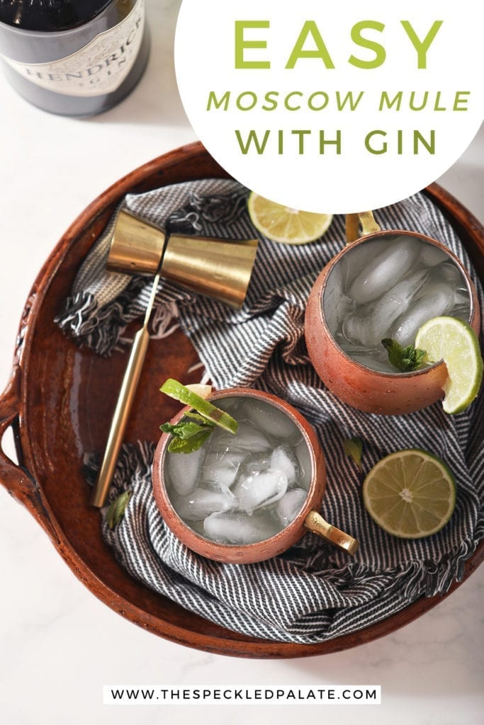 "Overhead of two mule mugs holding a Gin Gin Mule on top of a blue striped towel on a brown serving platter with text stating, ""How to Make a Moscow Mule with Gin"""
