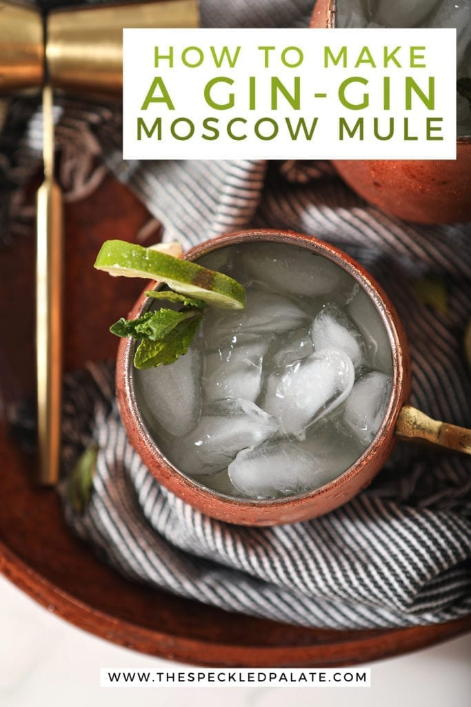 "Overhead close up of a mule mug holding a Gin Gin Mule on top of a blue striped towel on a brown serving platter with text stating, ""How to Make a Gin-Gin Moscow Mule"""