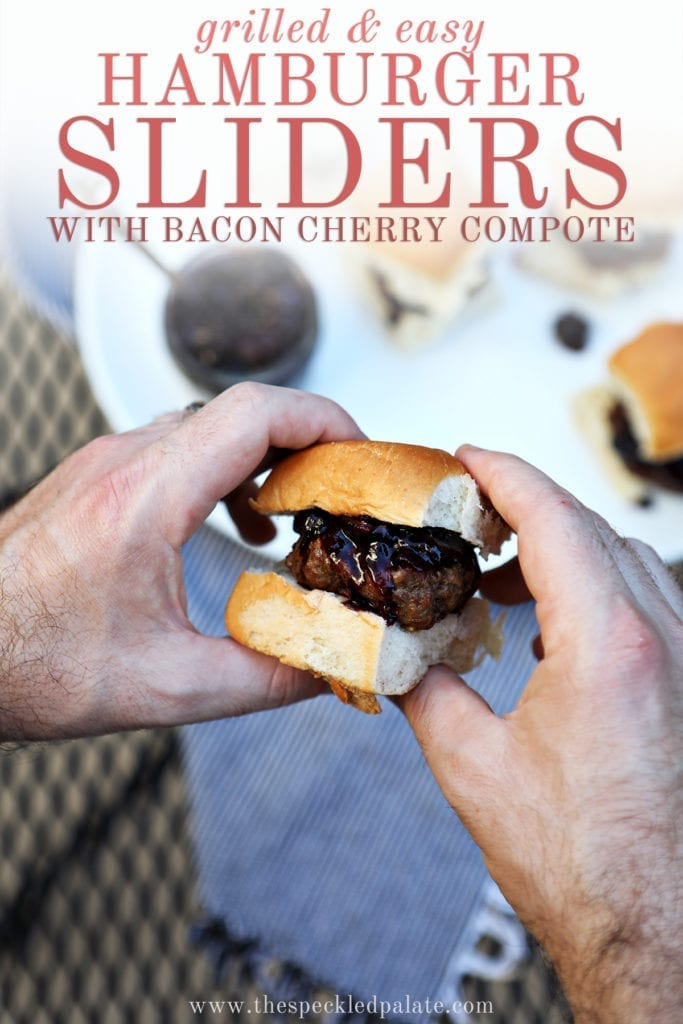 "A man holds a slider between his hands with a white platter of other sliders in the background with text ""grilled & easy hamburger sliders with bacon cherry compote"""