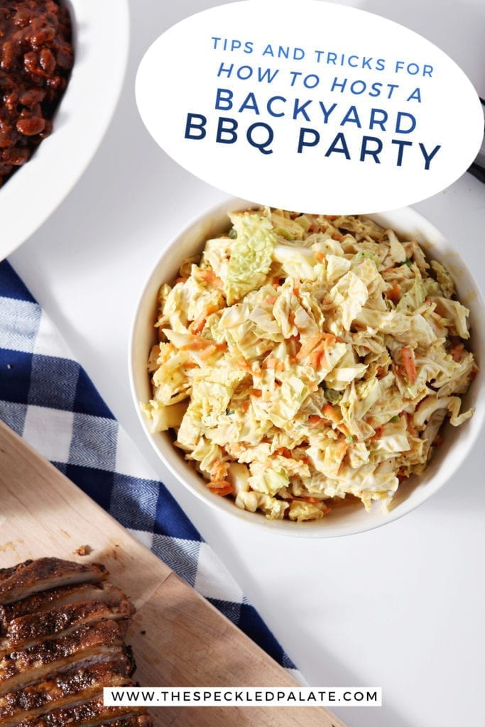 "A bowl of honey mustard coleslaw near a blue buffalo check napkin, a brisket on a wooden cutting board and baked beans with the text ""tips and tricks for how to host a backyard bbq party"""
