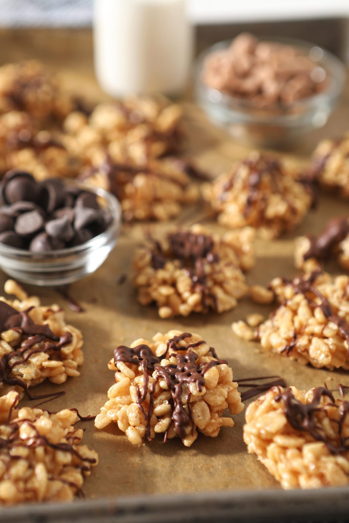 Several Chocolate Peanut Butter No Bake Cookies sit on a baking sheet lined in parchment with bowls of chocolate chips and butterscotch chips
