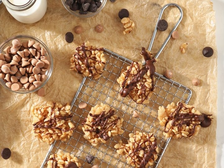 Several Chocolate Peanut Butter No Bake Cookies sit on a silver grate and brown parchment paper, surrounded by ingredients and a bottle of milk
