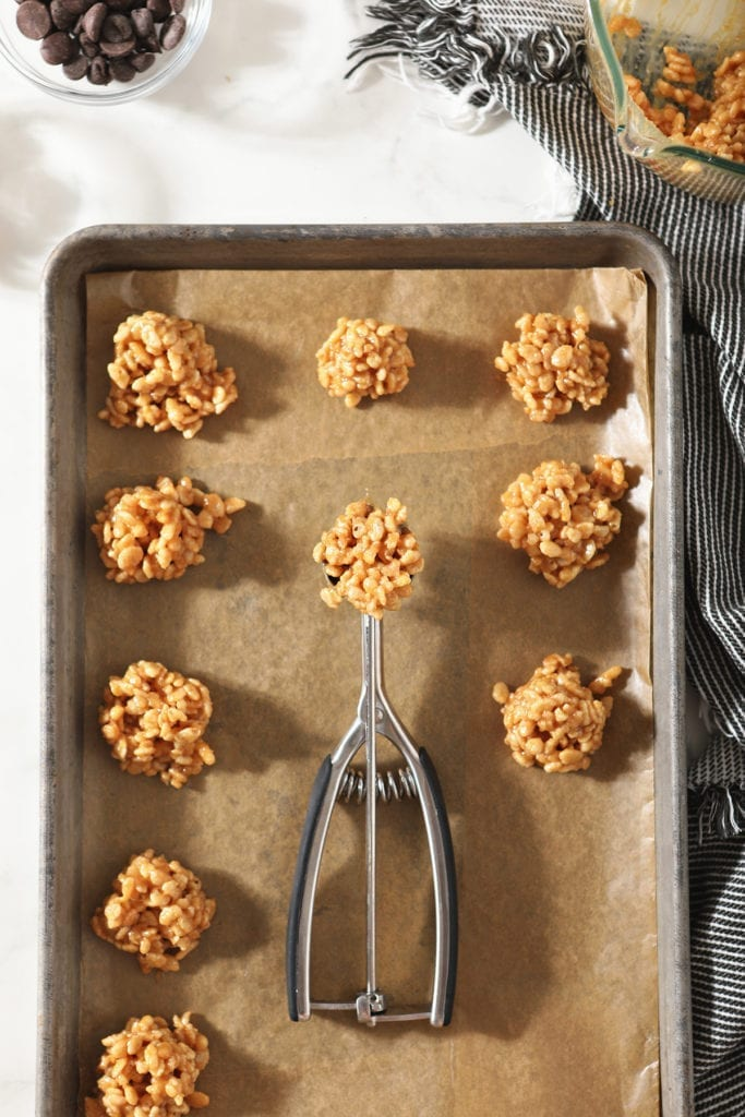 A cookie scoop holds a no bake cookie on a baking sheet with others