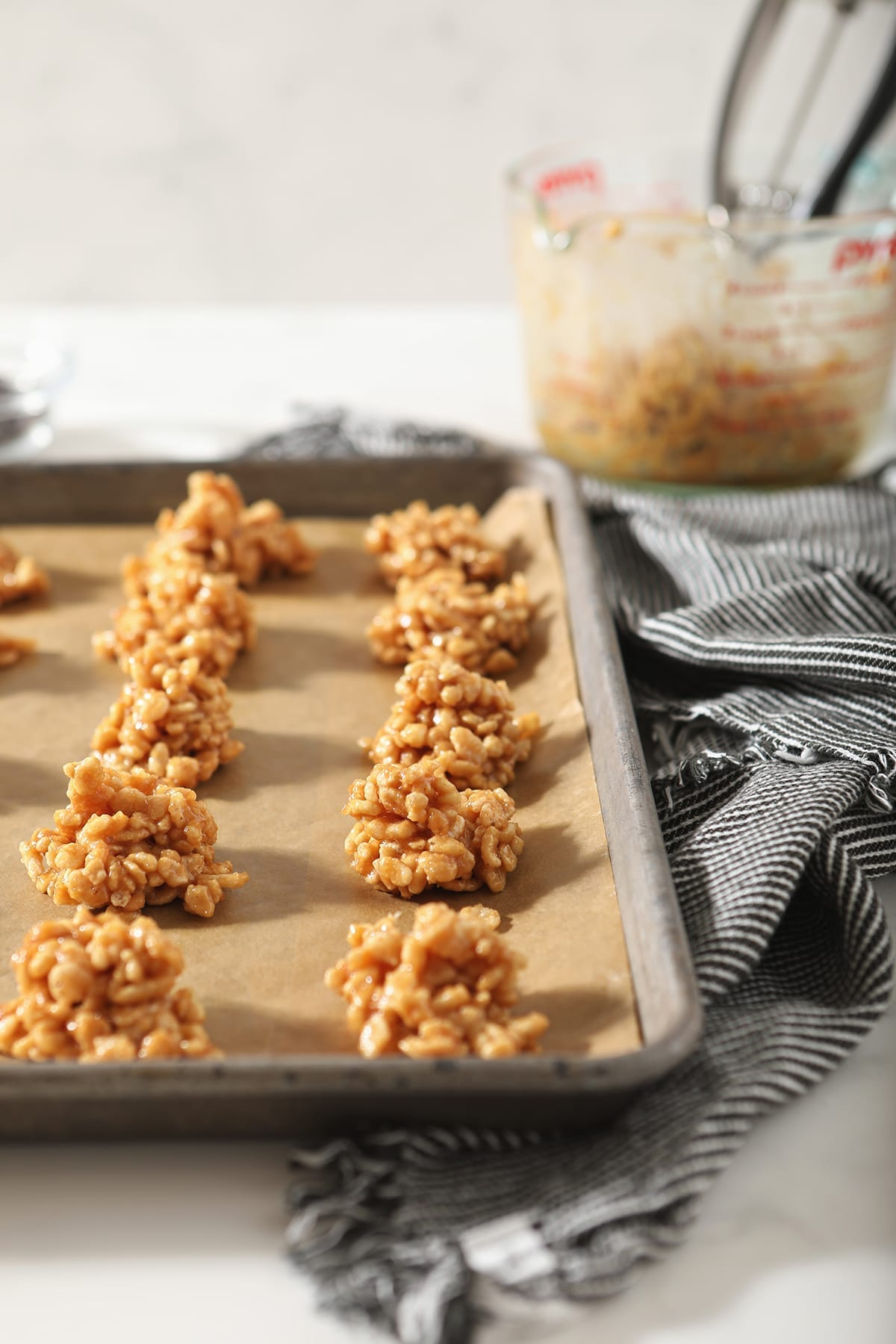 A lined baking sheet holds no bake peanut butter cookies on a marble surface with a grey and white towel