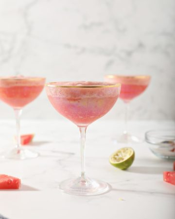 Three coup glasses hold a pink slush drink, surrounded by watermelons and limes on a marble surface