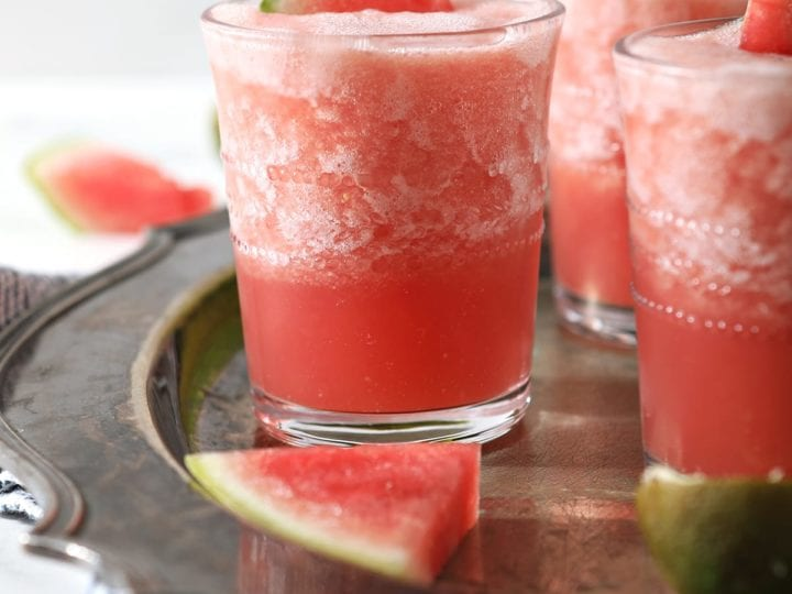 Three glasses holding pink slushy Watermelon Froses garnished with watermelon wedges on a silver platter