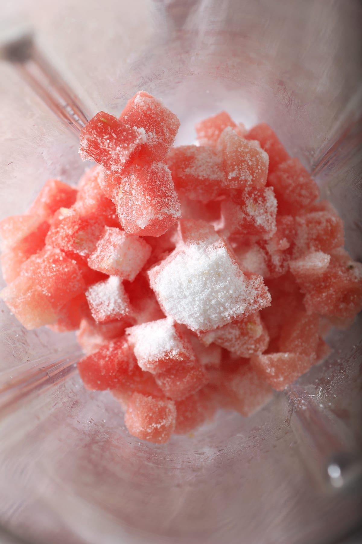 Close up of frozen watermelon cubes and granulated sugar in a blender