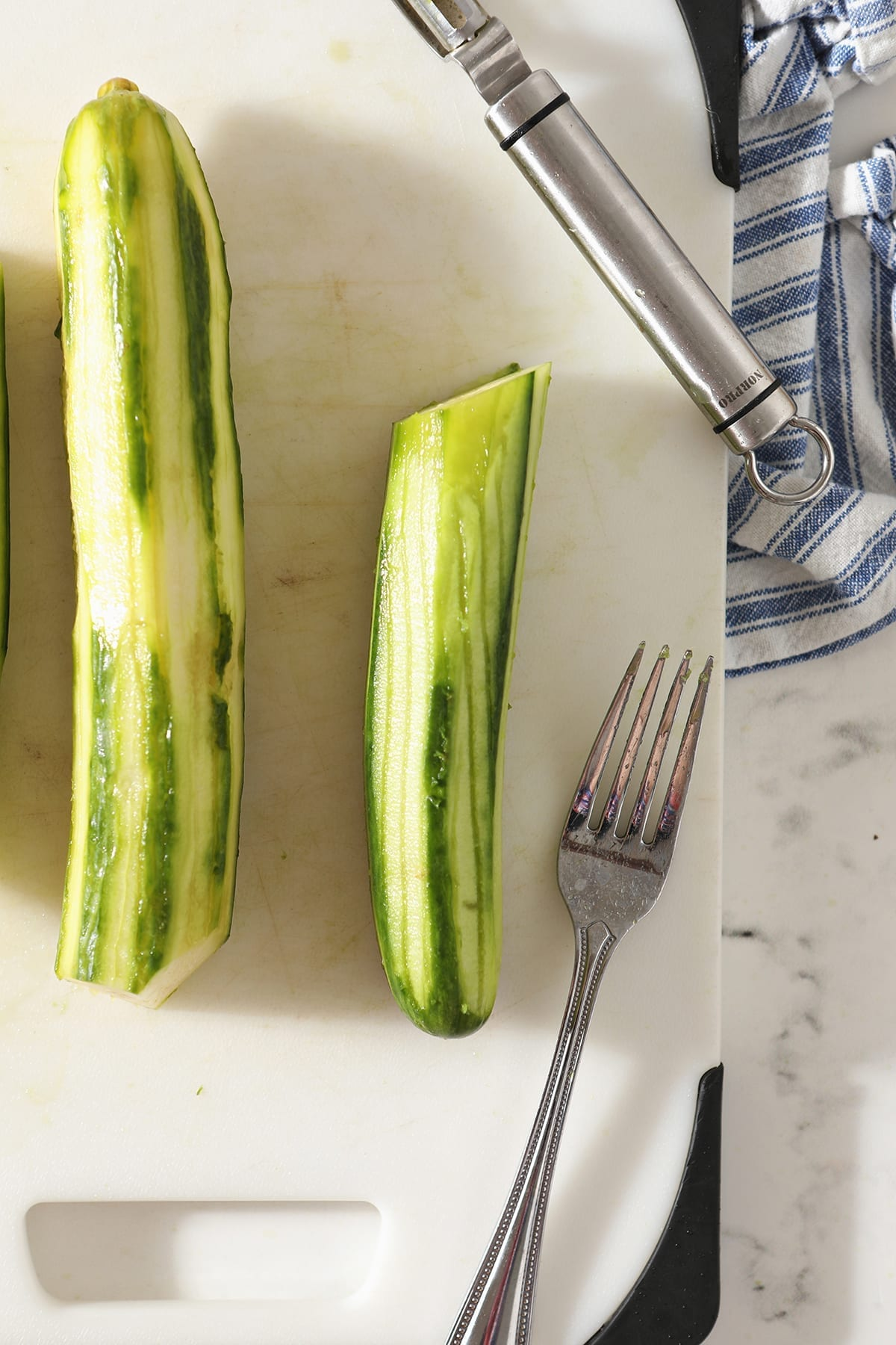 Two cucumbers, peeled and marked with a fork, sit on a white cutting board with a silver fork and a peeler