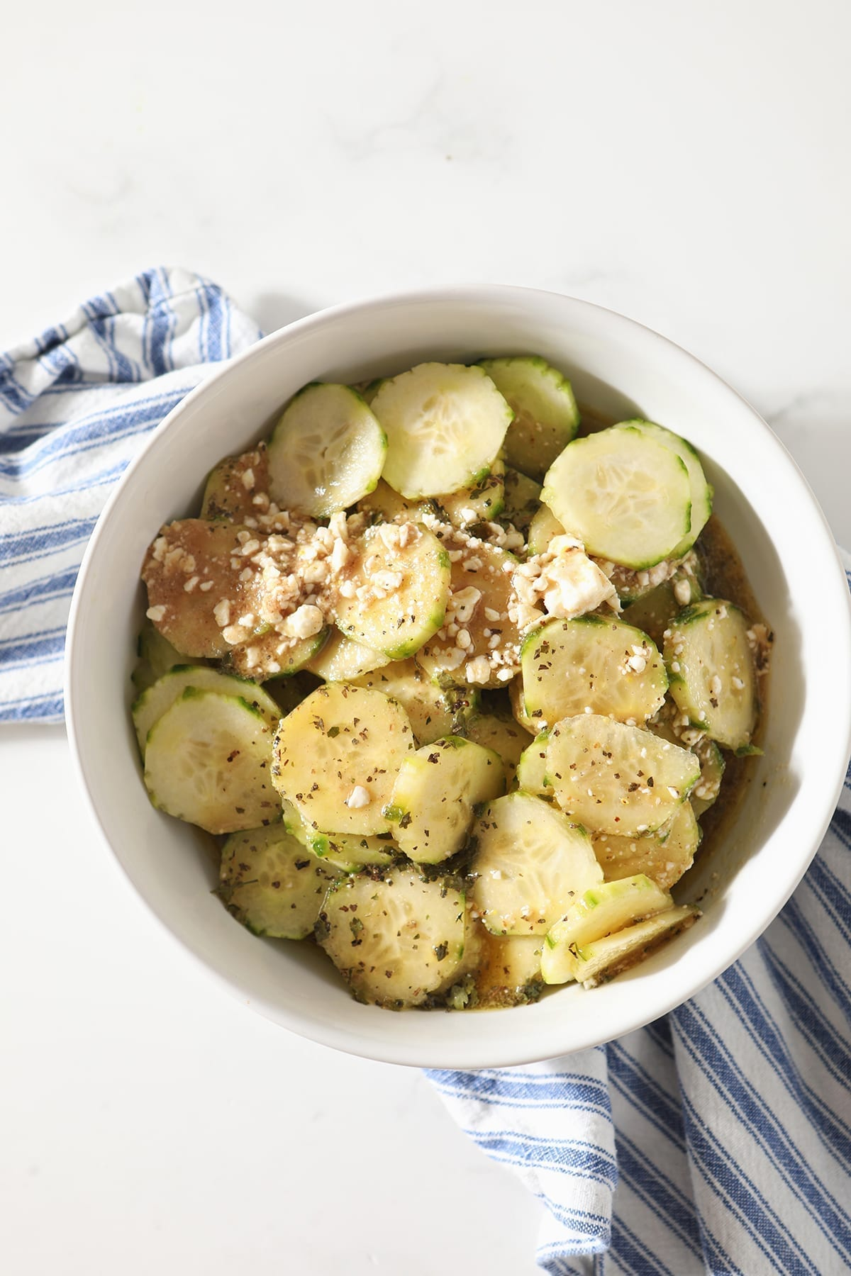 Easy Cucumber Salad with Feta Vinaigrette in a white bowl on top of a blue and white striped towel