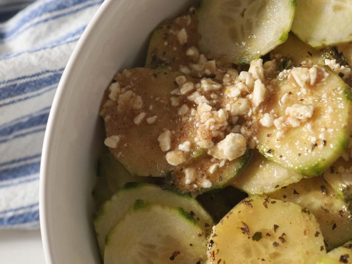 Close up of cucumbers and salad dressing in a white bowl on top of a blue striped towel