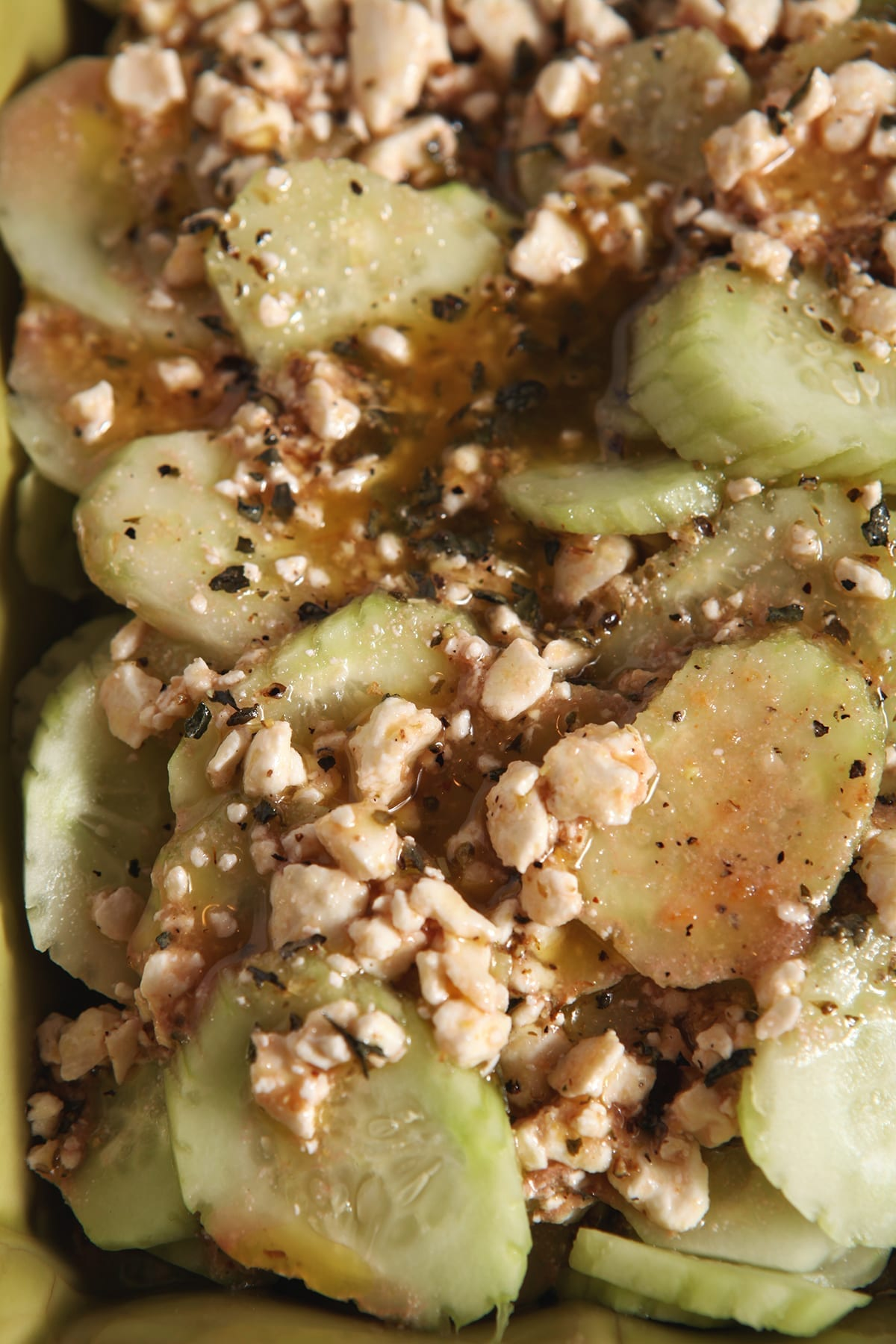 Close up of cucumbers and feta dressing in a green serving dish