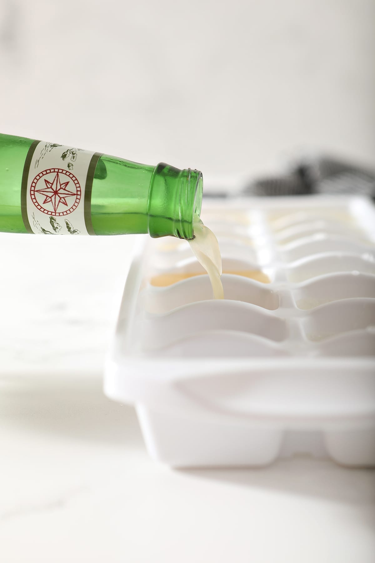 Ginger beer pours into a white ice cube tray