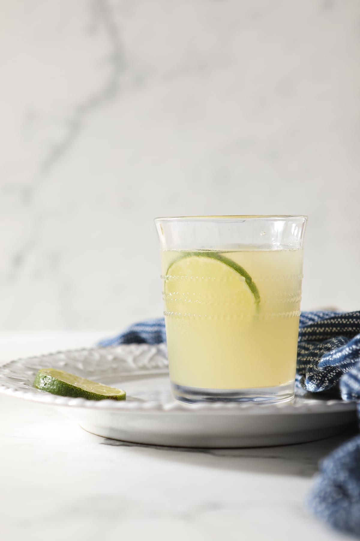 A Frozen Moscow Mule sits on a white plate on marble with slices of lime for garnish