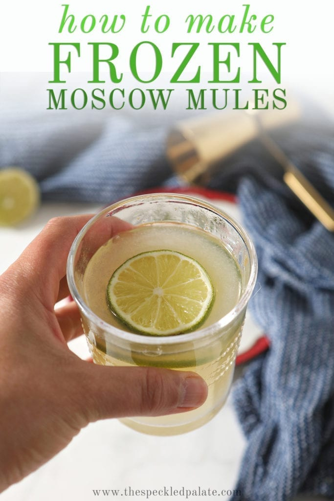 """A person holds a glass of the slushy cocktail garnished with a round of lime with the text """"How to Make Frozen Moscow Mules"""""""