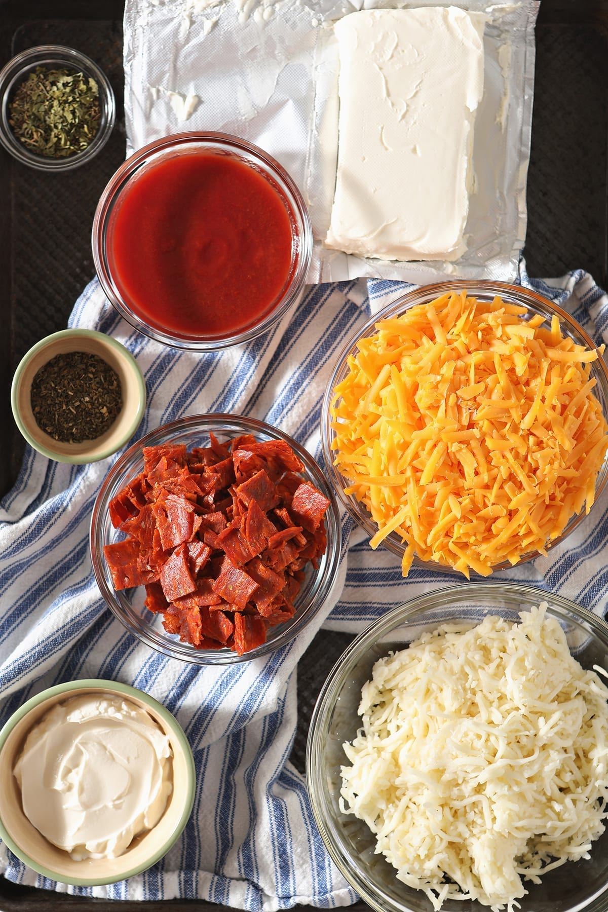 Ingredients for dip sit on a blue and white striped towel in a baking sheet