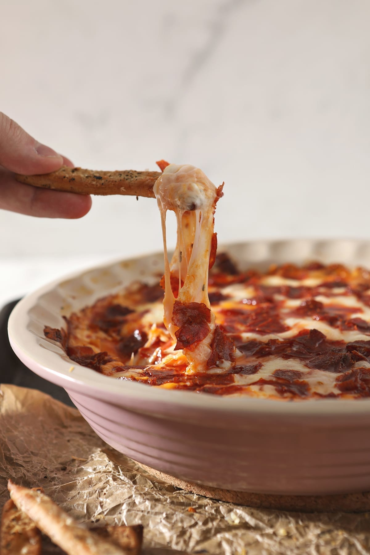 A breadstick lifts cheesy Pepperoni Dip out of a pie plate