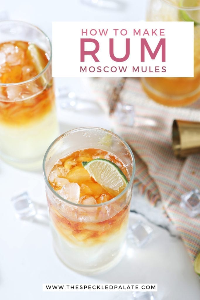 Three Rum Moscow Mules garnished with lime on marble with ice, lime wedges and a gold jigger with the text 'how to make rum moscow mules'