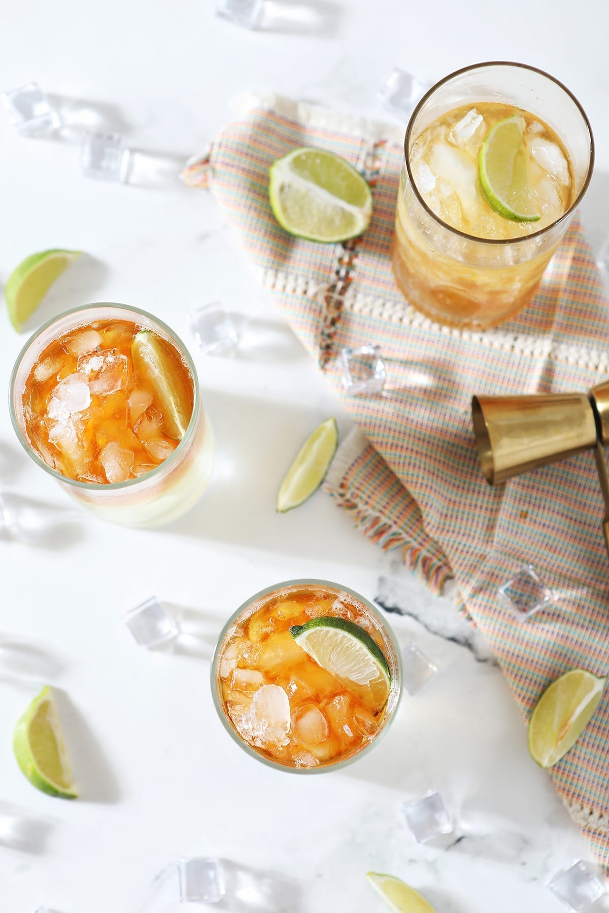 Overhead of three Rum Moscow Mules on marble, surrounded by lime wedges and ice cubes