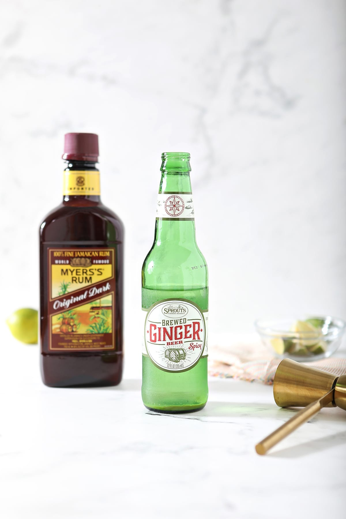 A bottle of ginger beer, a bottle of rum, a jigger and some limes on a marble backdrop