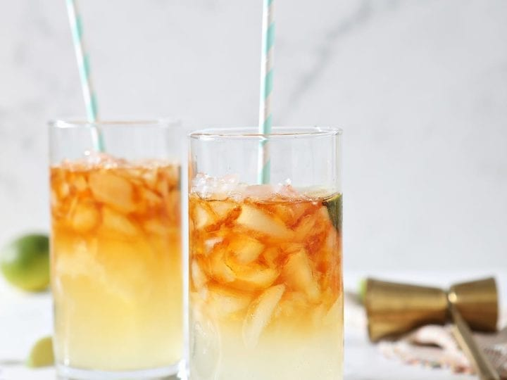 Two Dark and Stormy Drinks sit on marble surrounded by ice cubes, lime wedges and a gold jigger