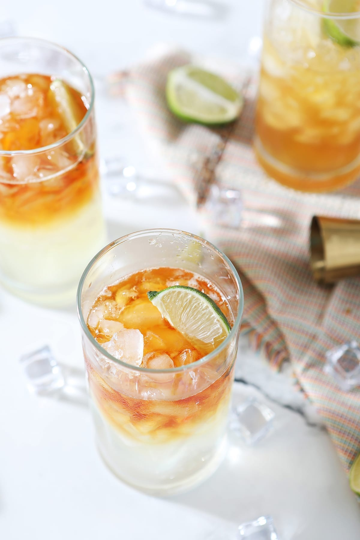 Three Rum Moscow Mules garnished with lime on marble with ice, lime wedges and a gold jigger