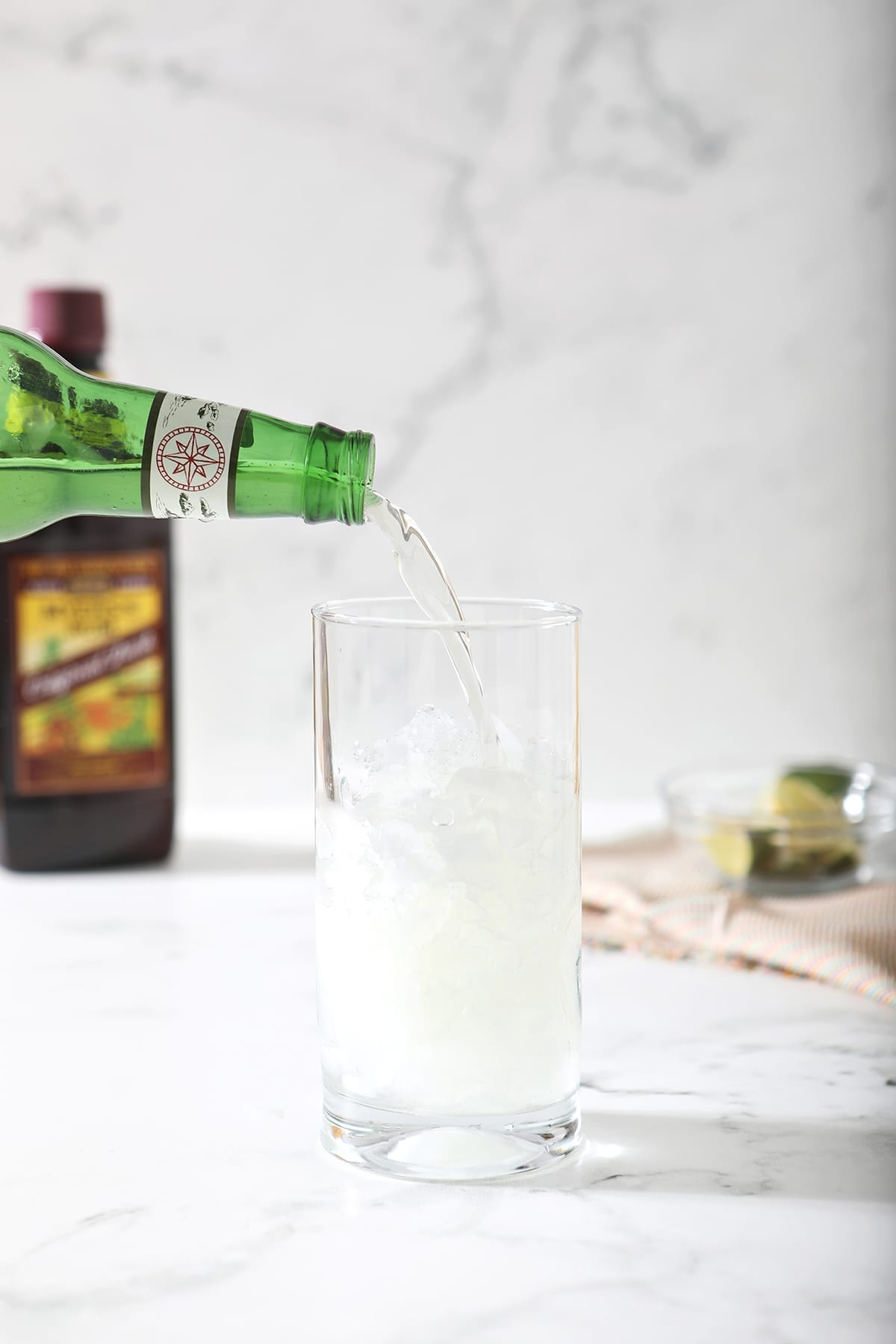 Ginger beer is poured into a highball glass with crushed ice cubes on marble