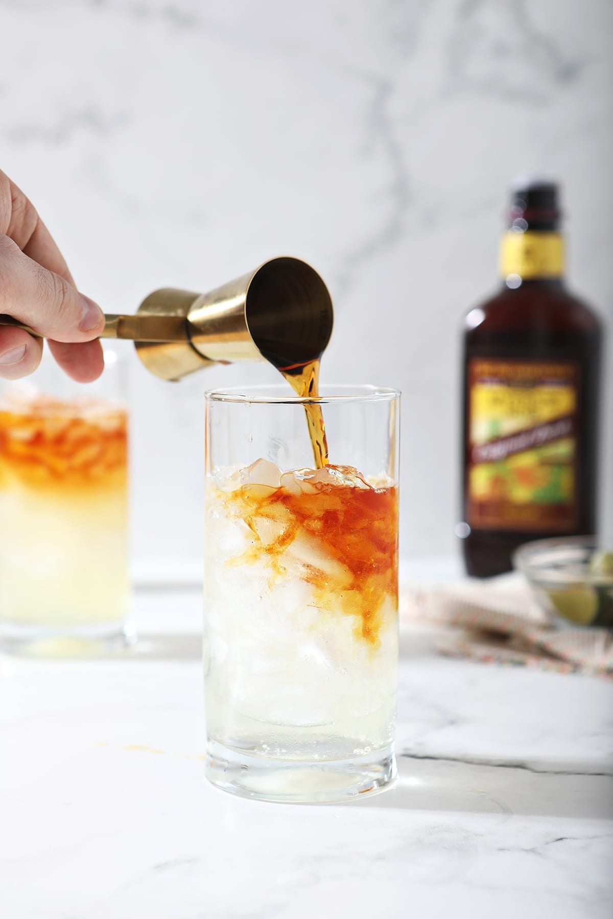 A jigger pours dark rum into a glass with ginger beer