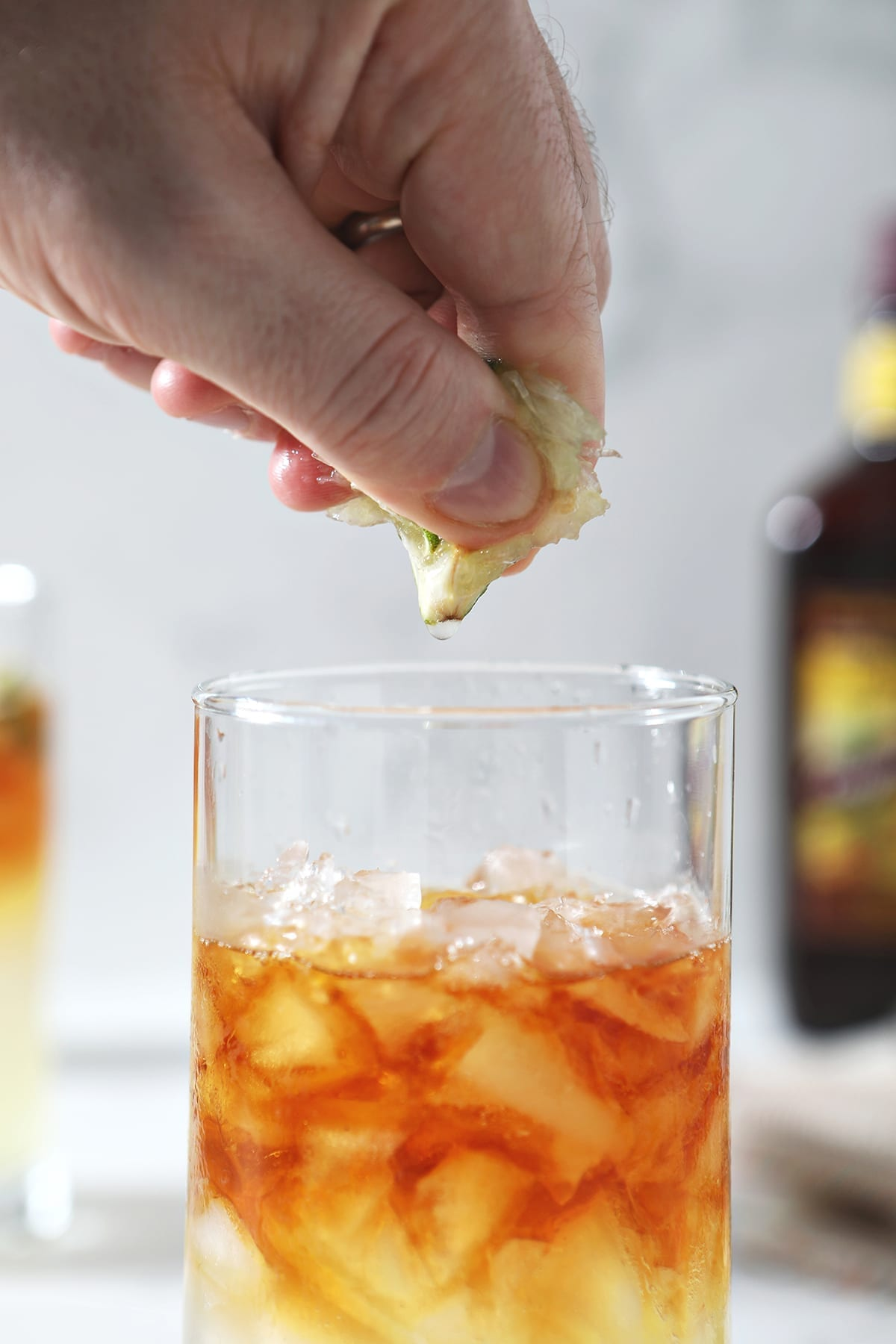 A lime wedge is squeezed into a highball glass over a brown liquid