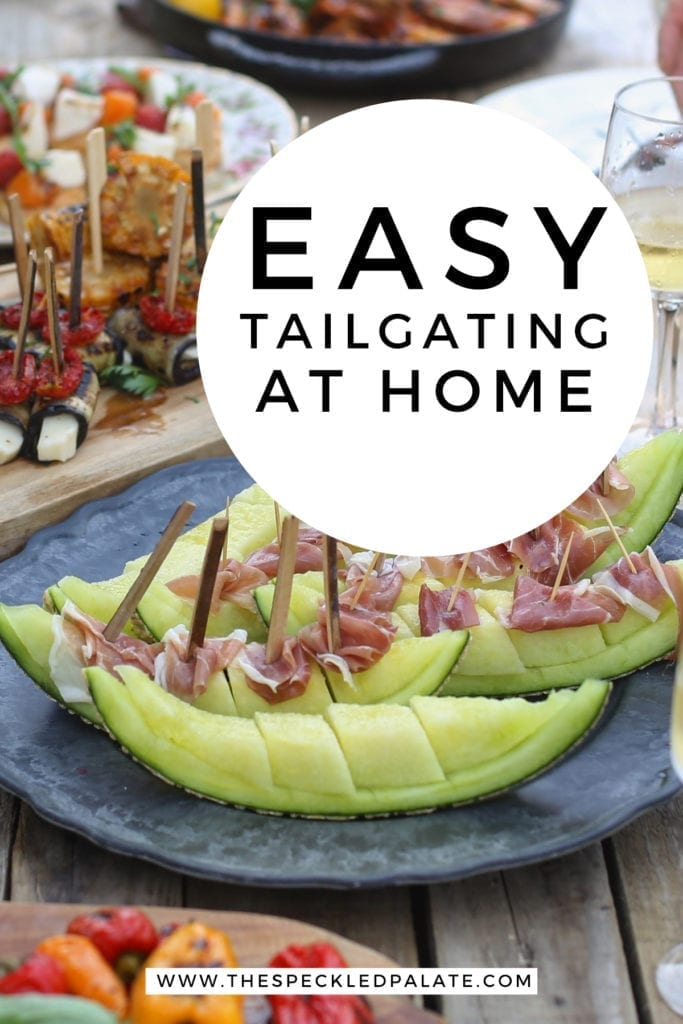 An outdoor table is laden with food and people sit around it with the text 'easy tailgating at home'