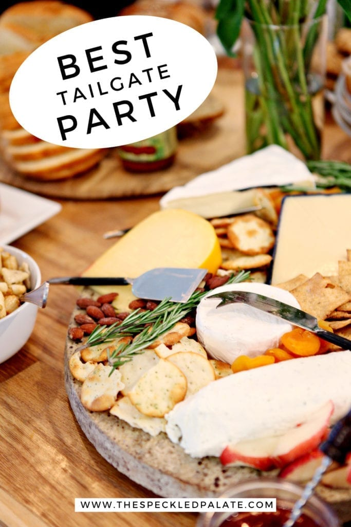 A cheese tray on a table with food at a potluck party with the text 'best tailgate party'