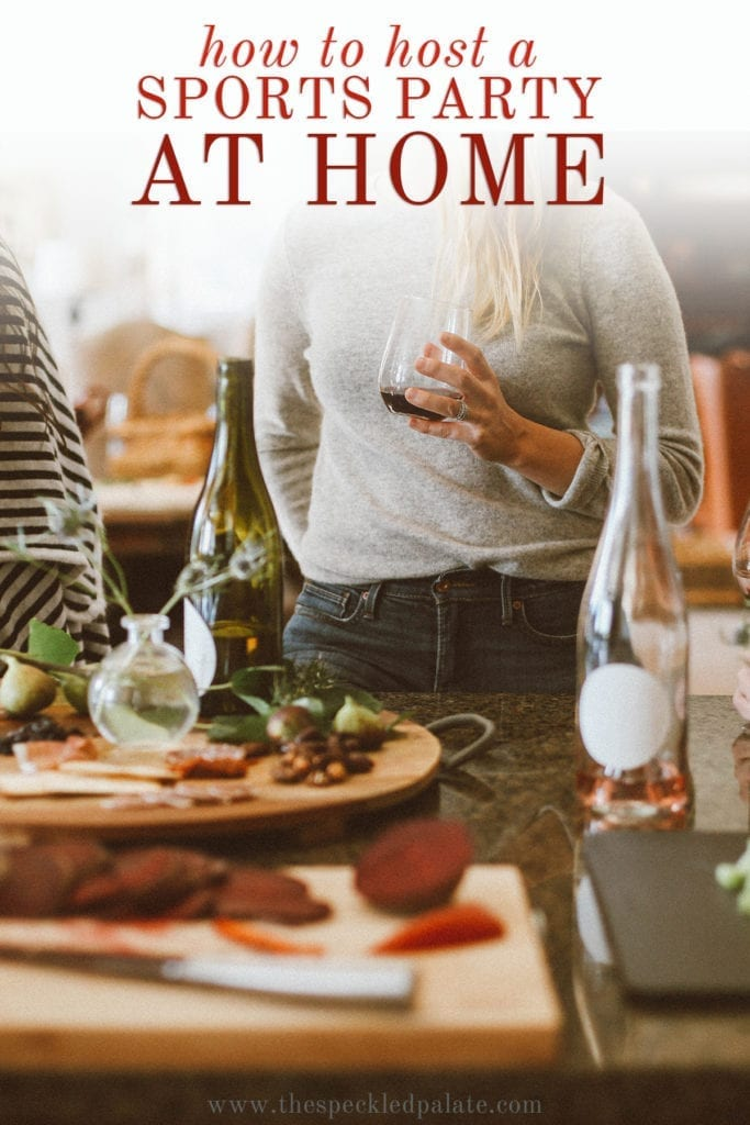 Women holding wine glasses stand by charcuterie and cheese boards with the text 'how to host a sports party at home'