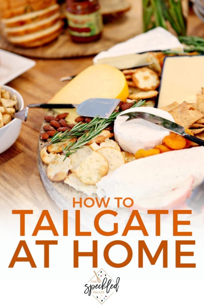 A cheese tray on a table with food at a potluck party with the text 'how to tailgate at home'