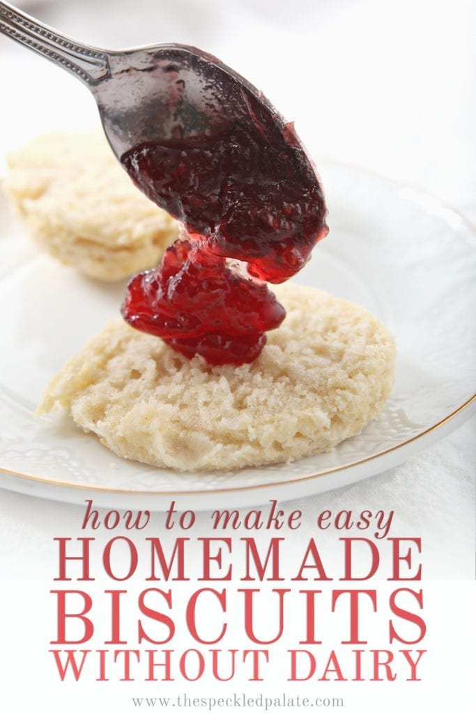 A spoon dollops raspberry jam into the middle of a vegan biscuit with the text 'how to make easy homemade biscuits without dairy'