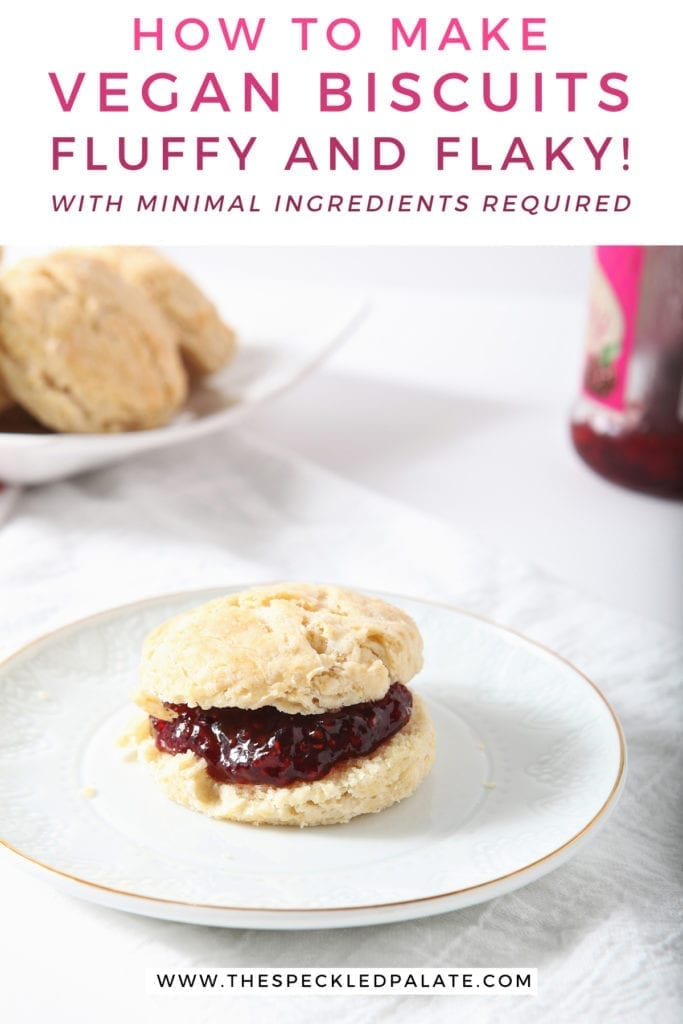 A biscuit with raspberry jam on a white plate with other biscuits and jam in the background with the text 'how to make vegan biscuits. fluffy and flaky! with minimal ingredients required.'