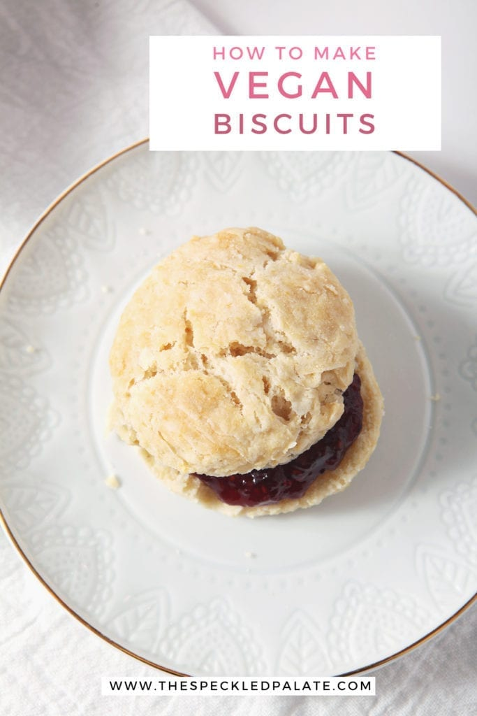 A vegan biscuit with jam on a white plate, from above, with the text 'how to make vegan biscuits'