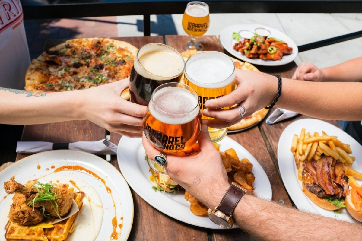 People at a table with food clink beer glasses together