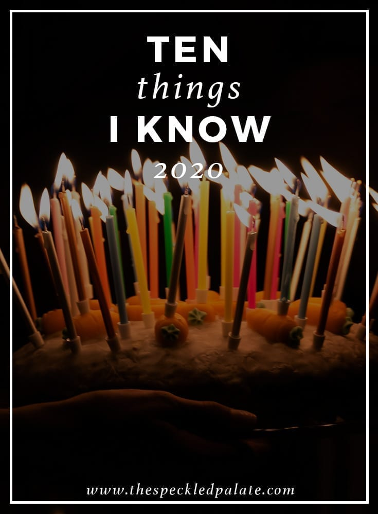 A birthday cake with lit candles on a dark background with the text overlay '10 things i know 2020'