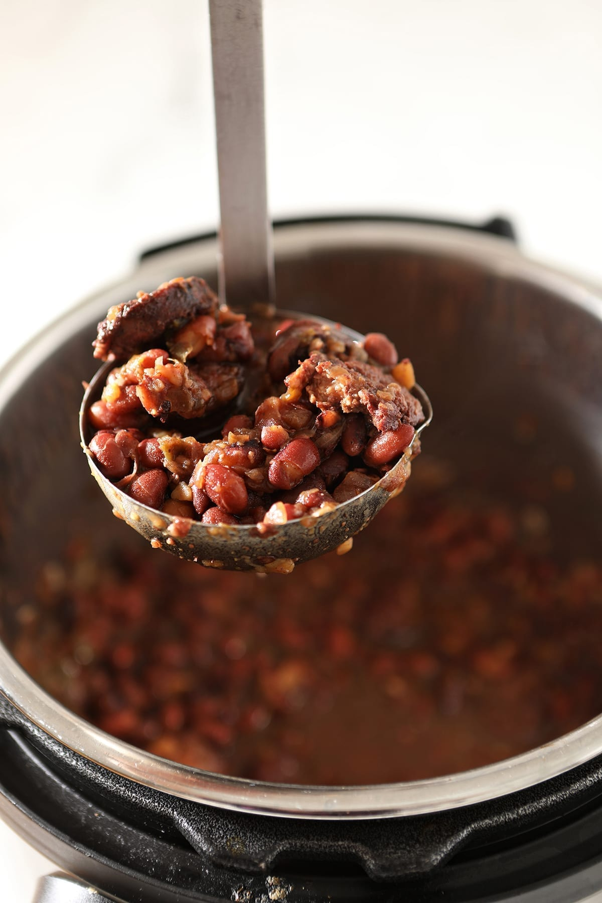 A ladle lifts red beans out of the Instant Pot, after cooking