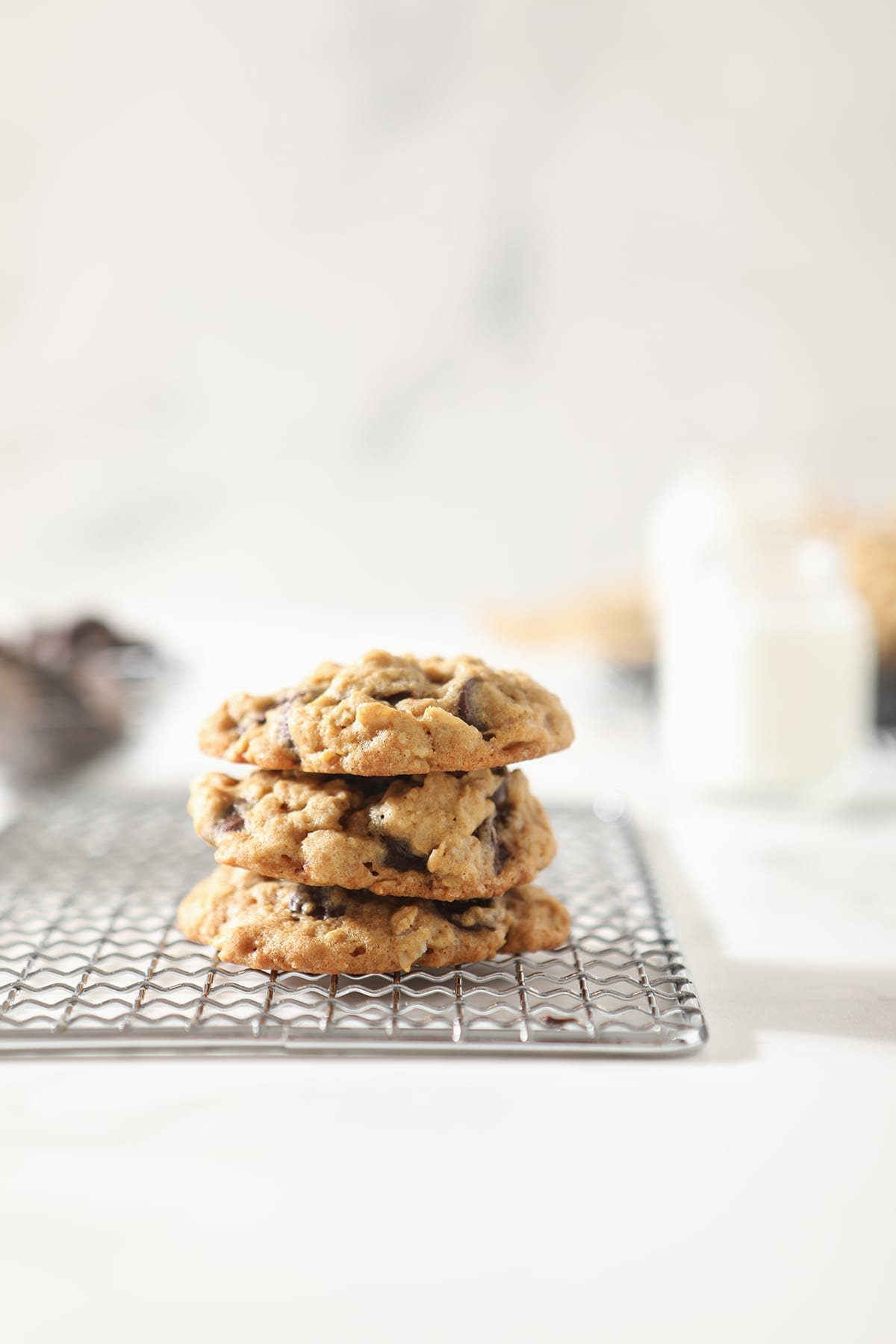 Three oatmeal chocolate chip cookies stacked on top of each other on a wire cooling rack
