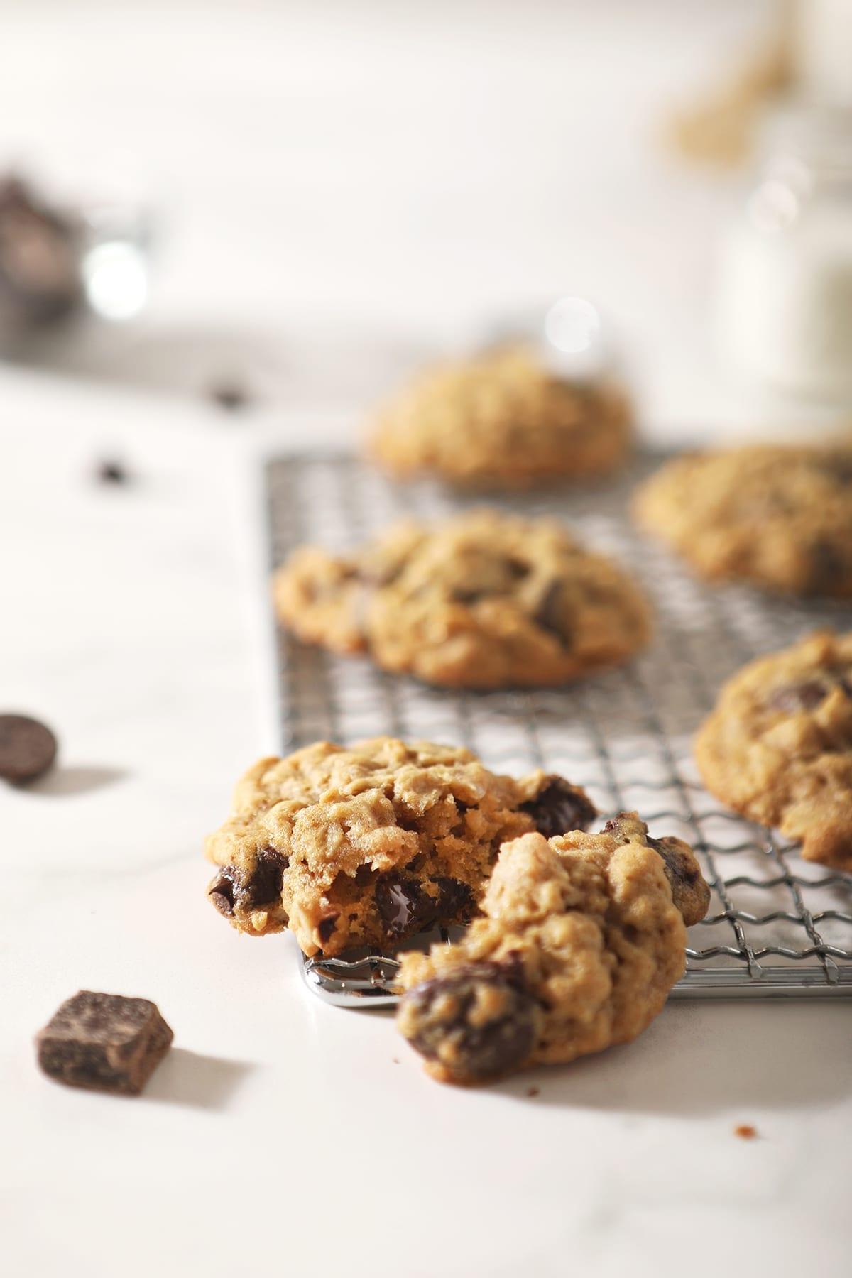 A halved oatmeal chocolate chip cookie on a wire cooling rack with other cookies behind it