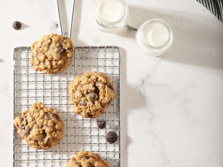 Several cookies on a wire cooling rack with milk around them