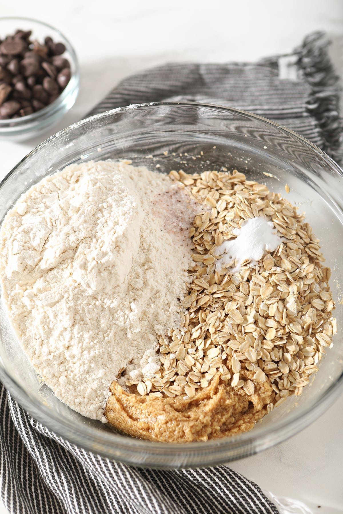 Flour, oats, leaveners and salt on top of wet ingredients in a bowl on marble
